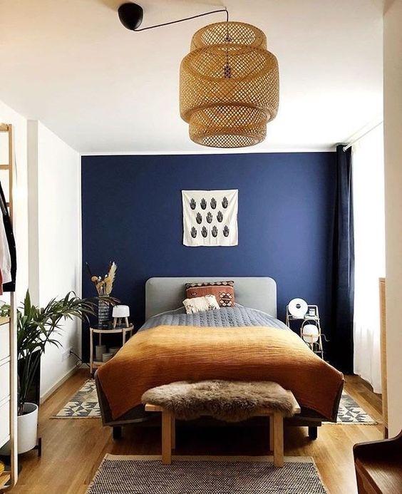 Quarto com parede azul marinho e detalhes marrons.