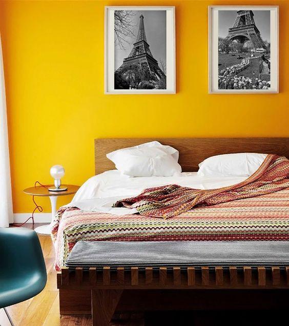Quarto com parede amarela com quadros em preto e branco.