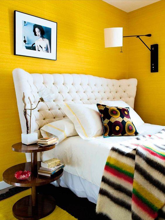 Quarto com paredes amarelas e cama branca.