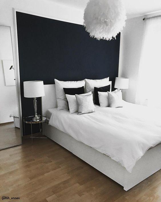Quarto branco com uma parede preta.