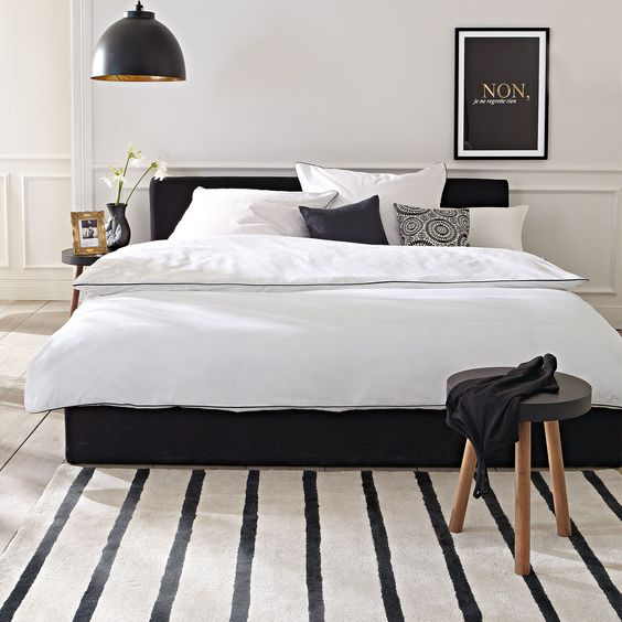 Quarto branco com cama preta.