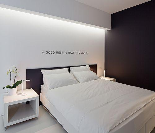 Quarto com cabeceira da cama preta combinando com uma das paredes.