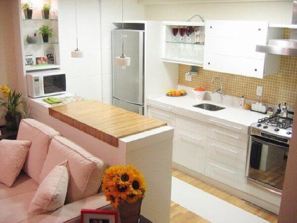 Decoração com armário branco e bancada de madeira.