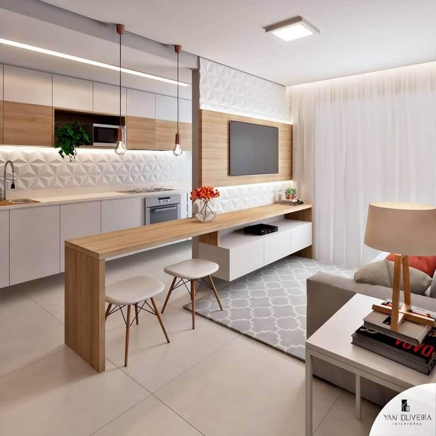 Cozinha americana pequena branca com bancada de madeira.