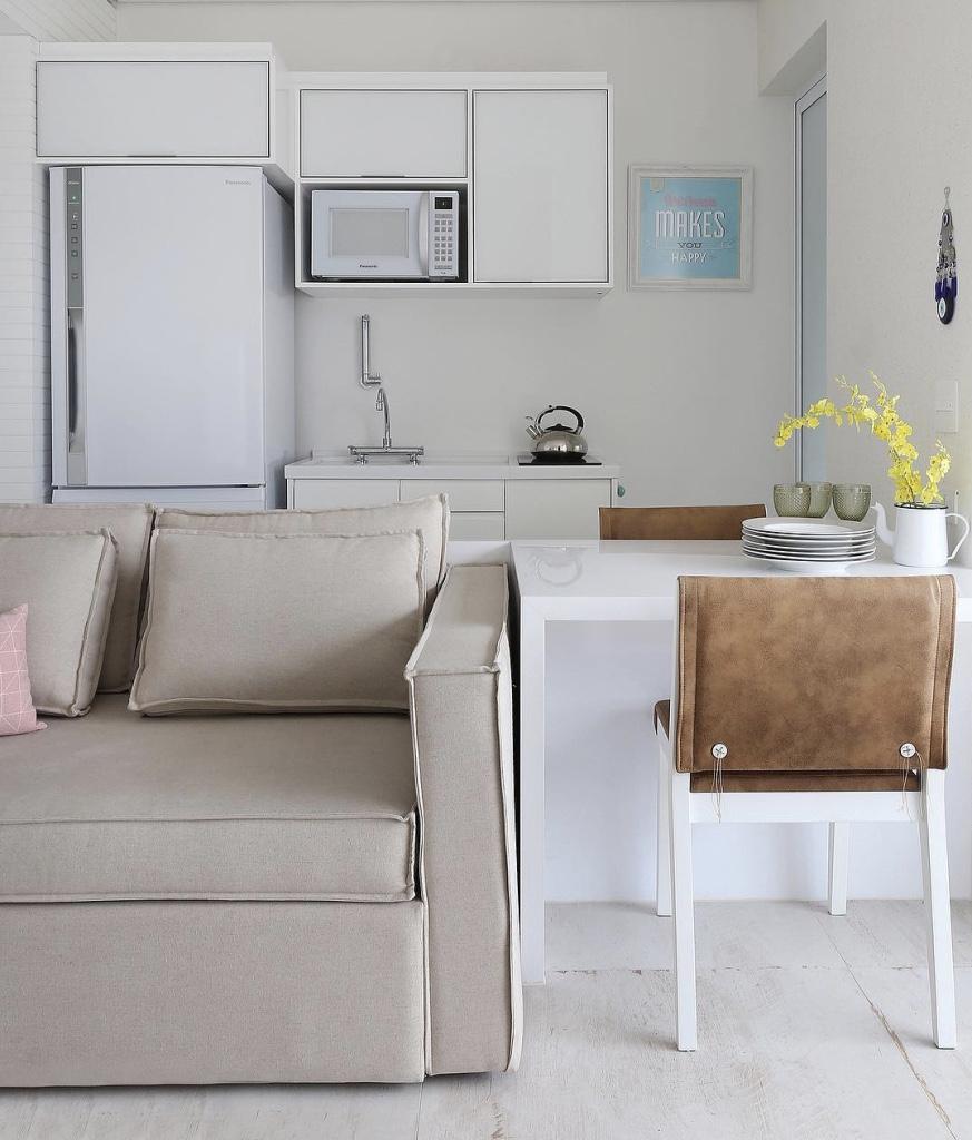 Decoração simples com armário branco e mesa de madeira.