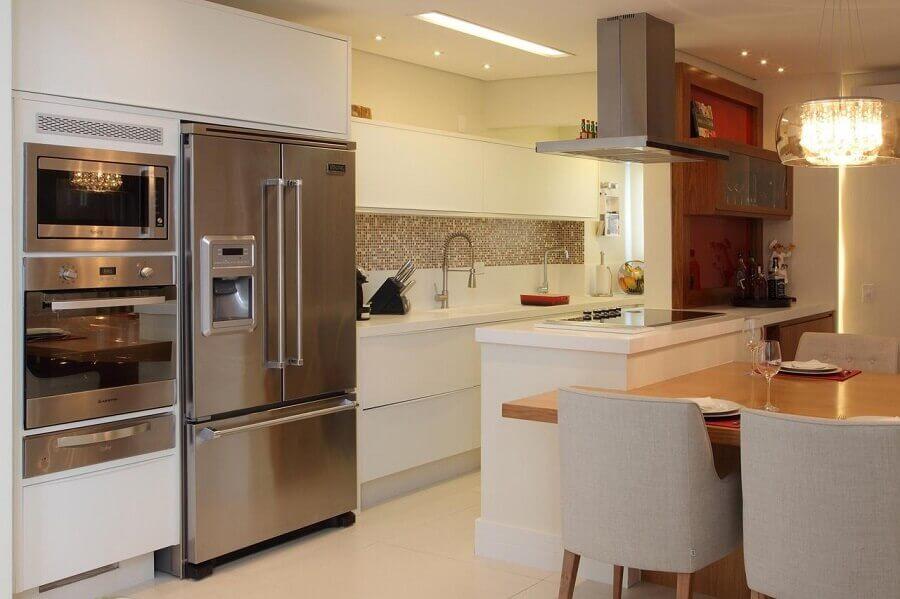 Cozinha americana pequena com armário branco e decoração elegante.