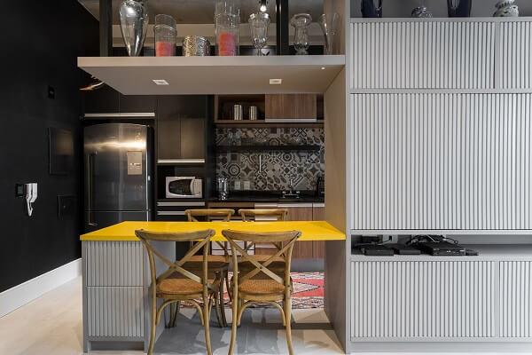 Decoração moderna com armários pretos e mesa amarela.