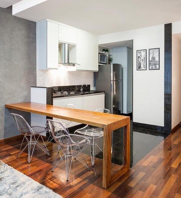 Cozinha americana pequena com bancada de madeira rústica.