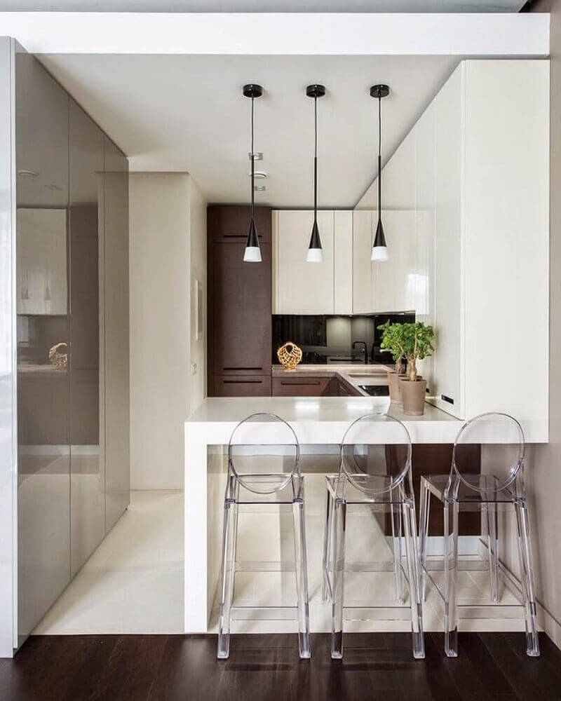 Decoração moderna com armários brancos e marrons, bancada branca e banquetas de acrílico.