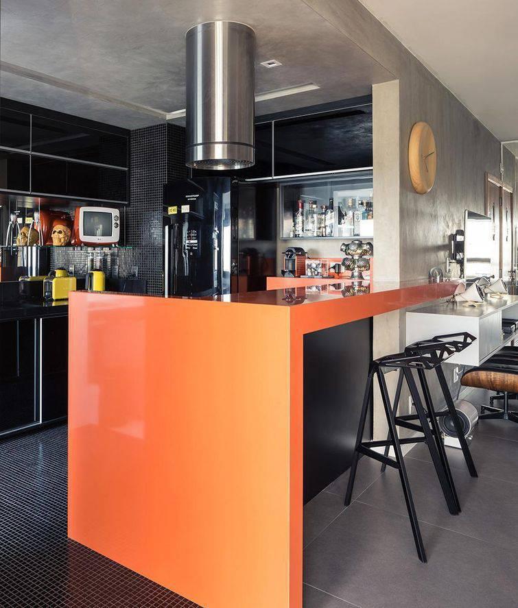 Cozinha americana pequena preta com bancada laranja.