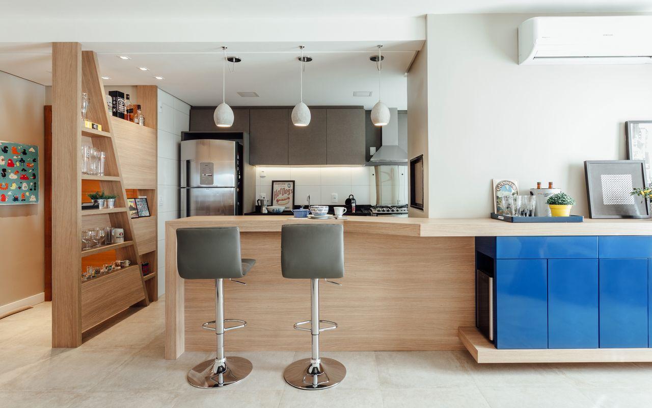 Cozinha americana pequena moderna com bancada de madeira e banqueta cinza.
