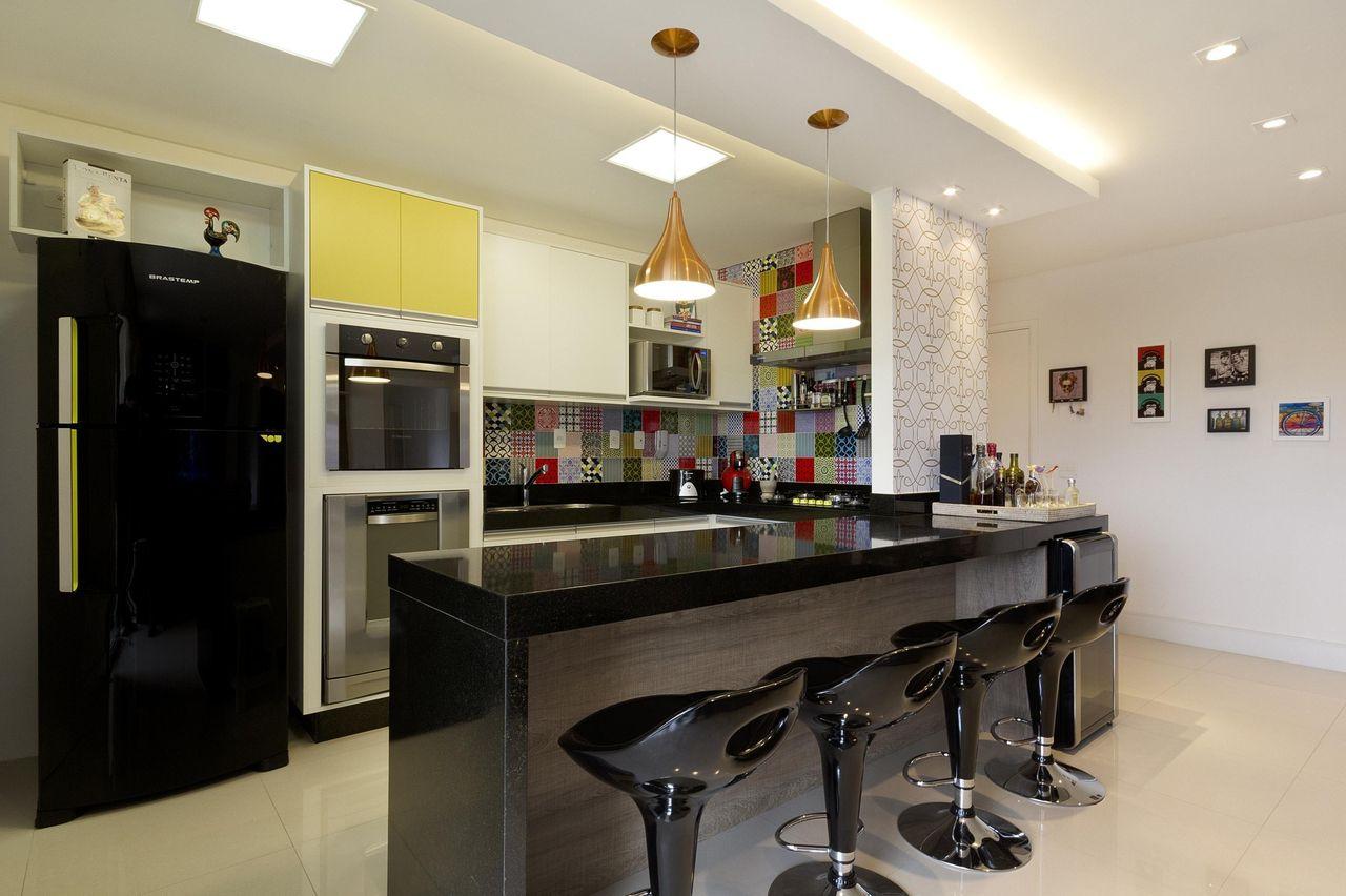 Decoração moderna com azulejo colorido, geladeira preta e bancada de granito.