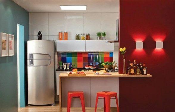 Cozinha americana pequena com azulejo colorido e bancada de madeira.