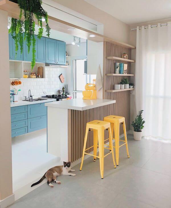 Cozinha americana pequena com armários azuis e bancada de madeira.