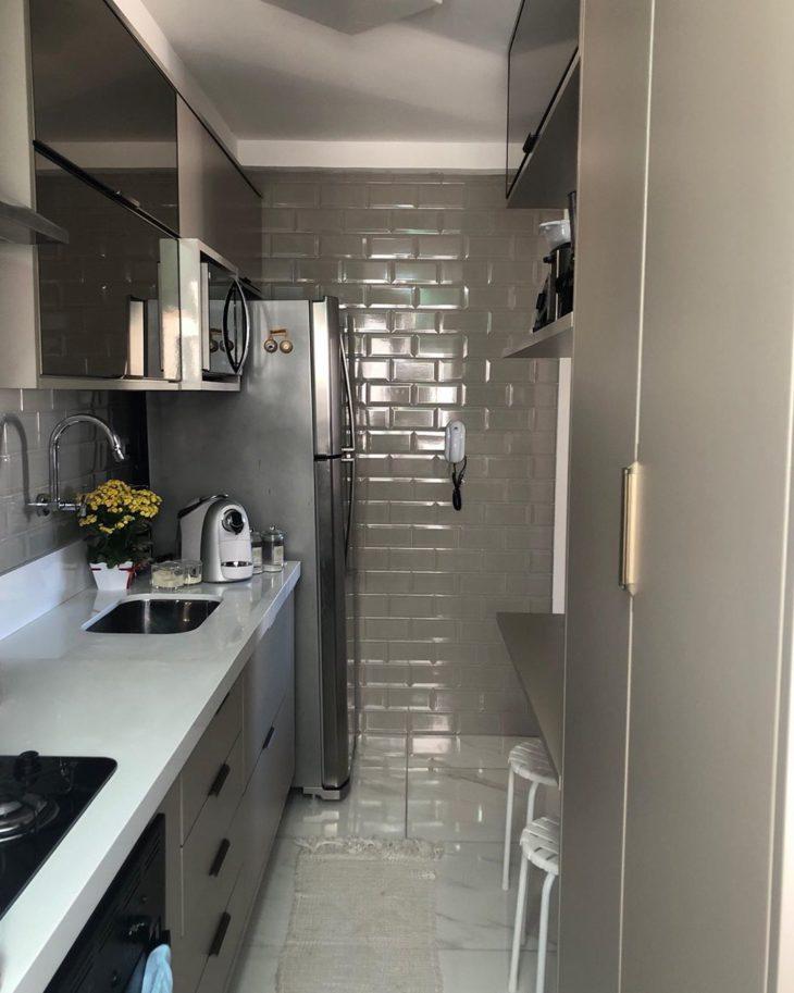 Decoração com armários cinzas e parede com azulejo de tijolinho branco.
