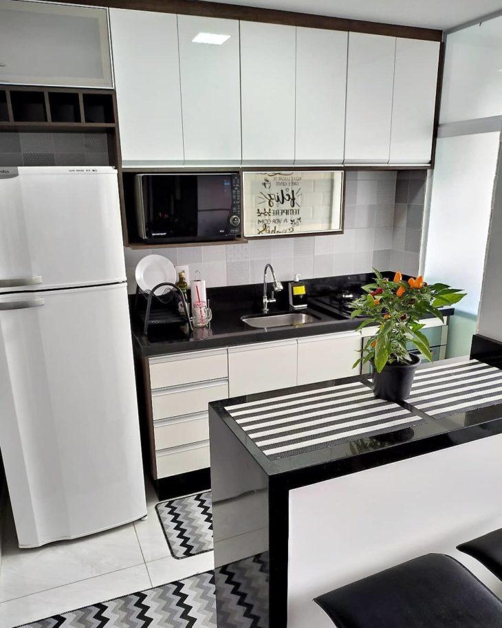 Decoração simples com armário branco e bancada de granito.