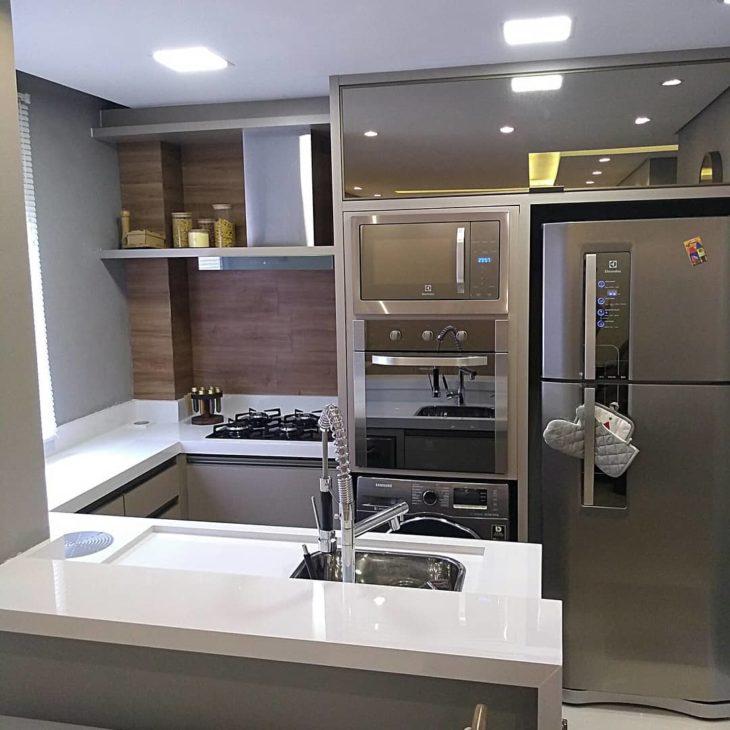 Decoração moderna com armário espelhado e bancada de mármore.