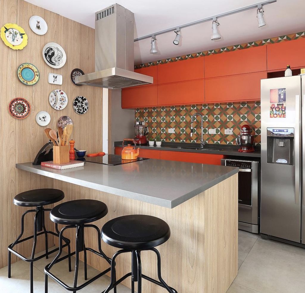 Decoração com armário laranja e azulejo decorado colorido.