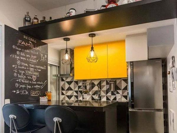 Decoração moderna com armário amarelo, bancada de granito e azulejo decorado.