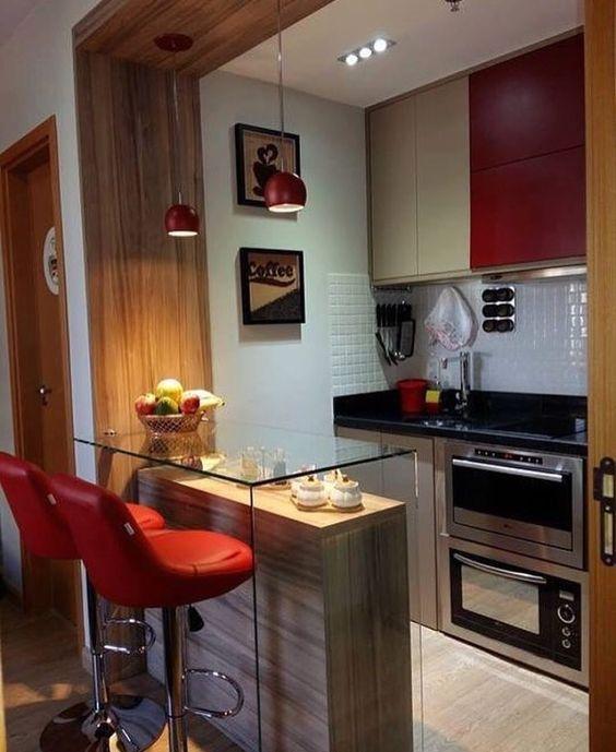Cozinha americana pequena com bancada de vidro e armário vermelho.