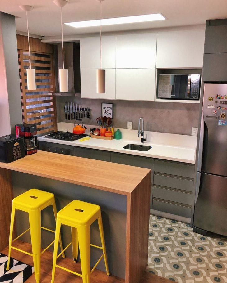 Cozinha americana pequena com armário branca, parede de cimento queimado e bancada de madeira.