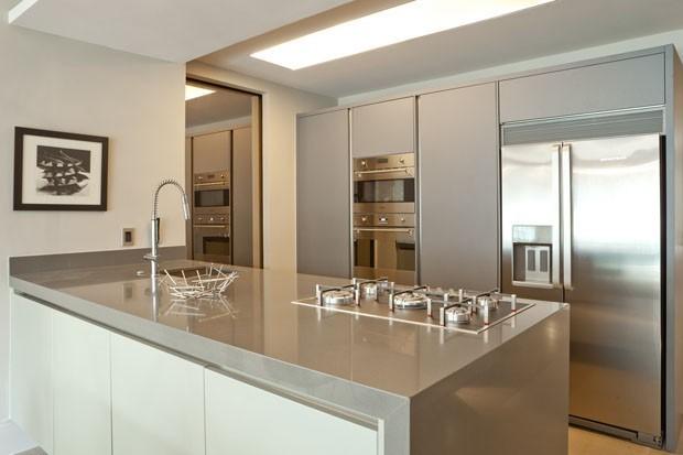Decoração moderna com armário cinza, geladeira inox e cooktop.