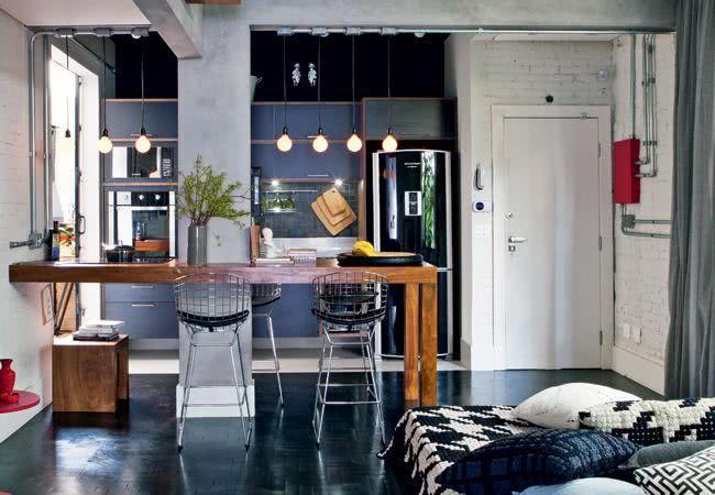 Decoração moderna com armário cinza, geladeira preta e bancada de madeira.