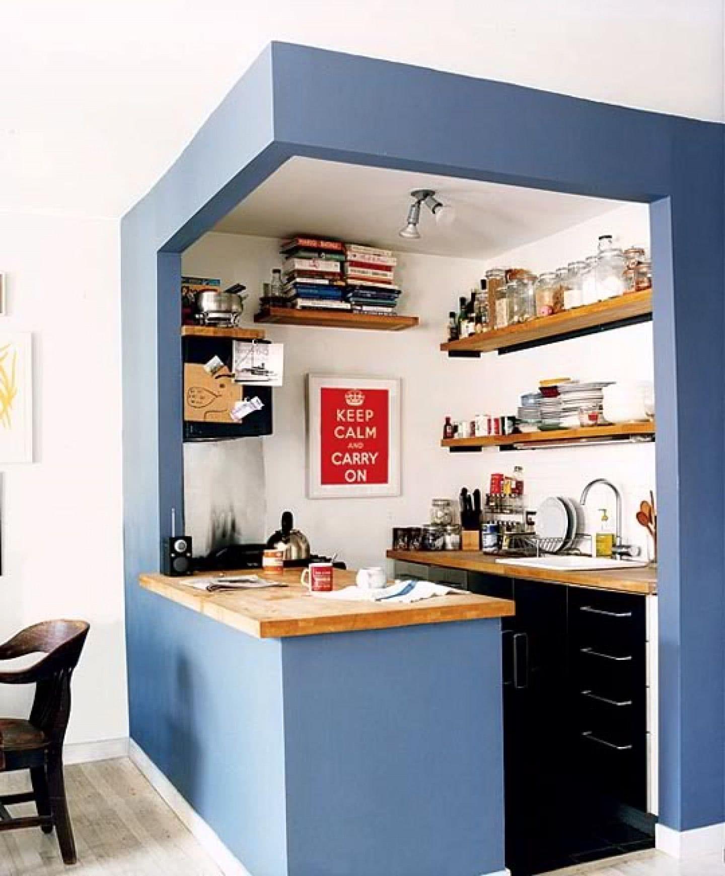 Decoração simples com armário preto, prateleira de madeira e bancada de madeira.