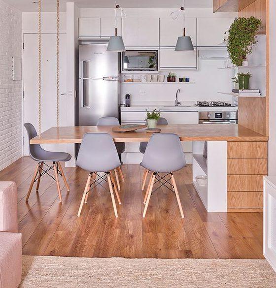 Cozinha americana pequena com armários brancos e mesa de madeira suspensa.