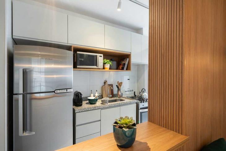 Decoração simples com armários brancos e bancada de madeira.