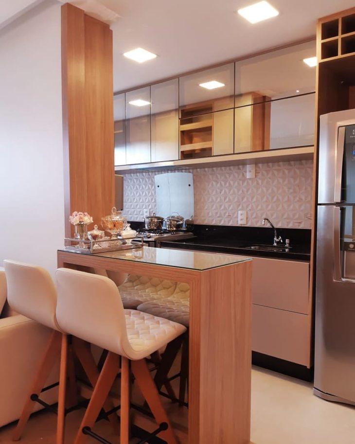 Cozinha americana pequena com armário espelhado e bancada de vidro.