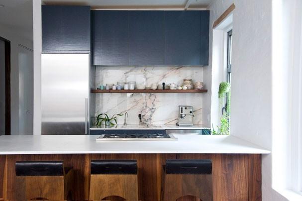 Decoração moderna com armário azul e minimalista, revestimento de mármore e bancada de granito.