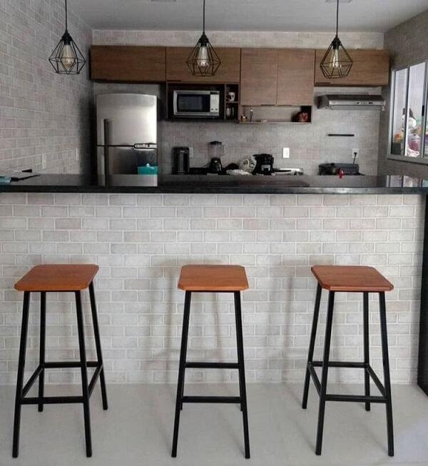 Decoração moderna com bancada de granito, banquetas simples e revestimento de tijolinho.