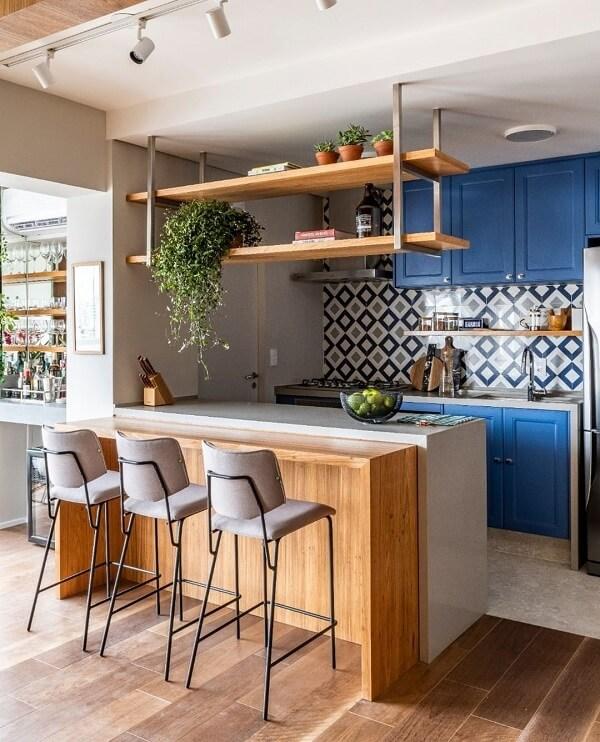 Decoração moderna com armários azuis e bancada de madeira.