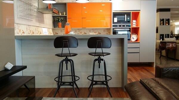 Decoração com armário laranja e cinza.