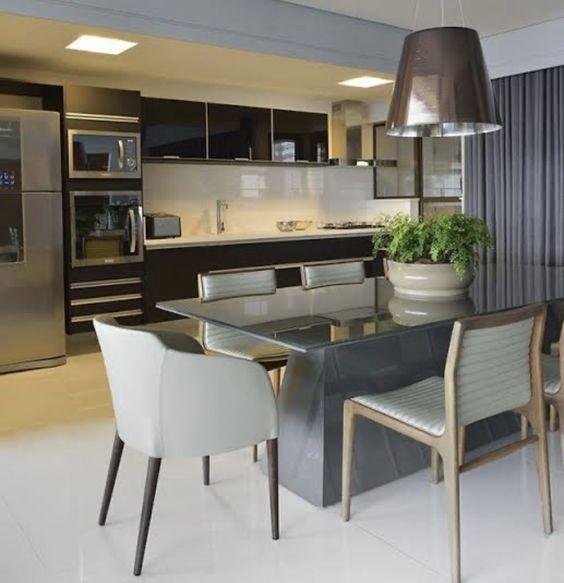 sala de jantar com pendente de metal e cozinha americana