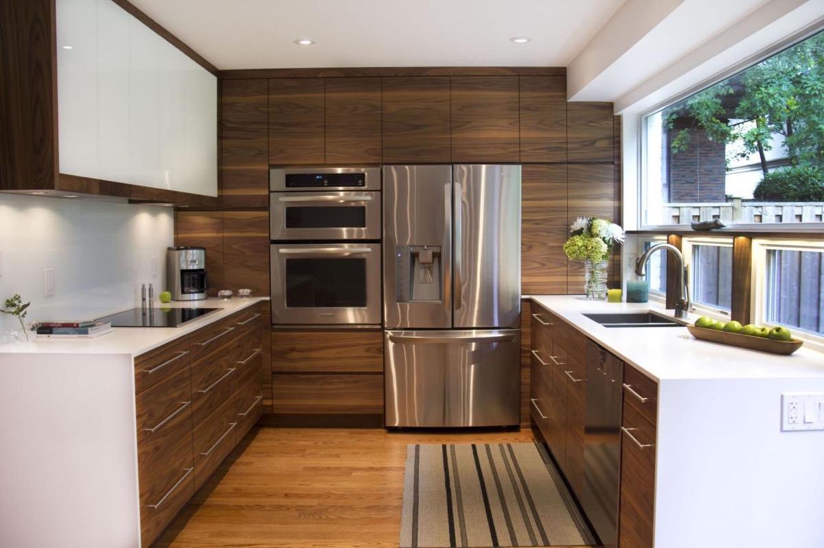 Cozinha em U planejada com armários de madeira e cooktop.