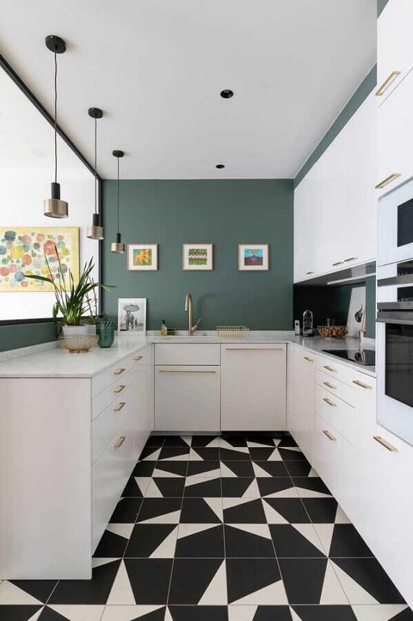 Decoração moderna com piso geométrico preto e branco e parede verde.