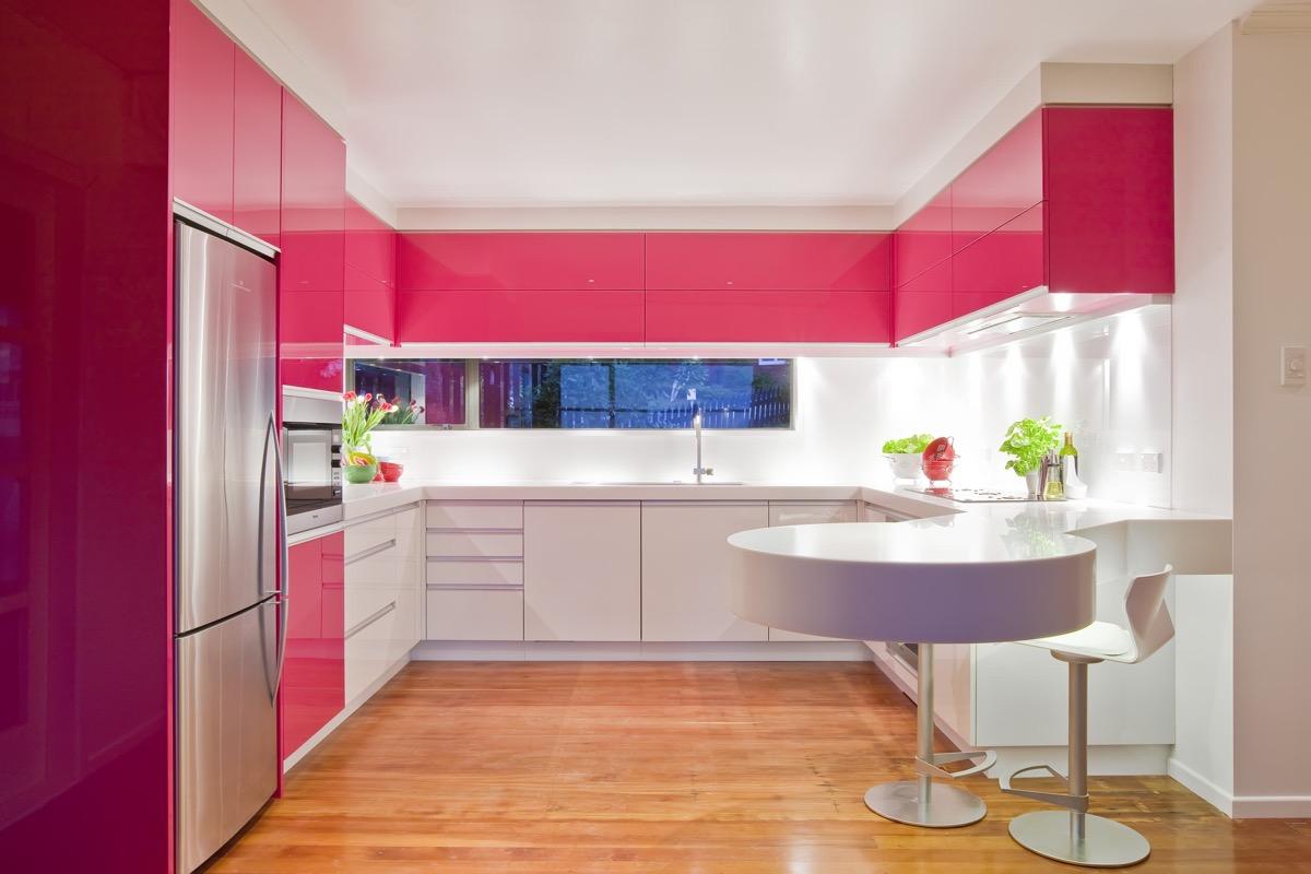 Cozinha em U moderna com armário rosa.