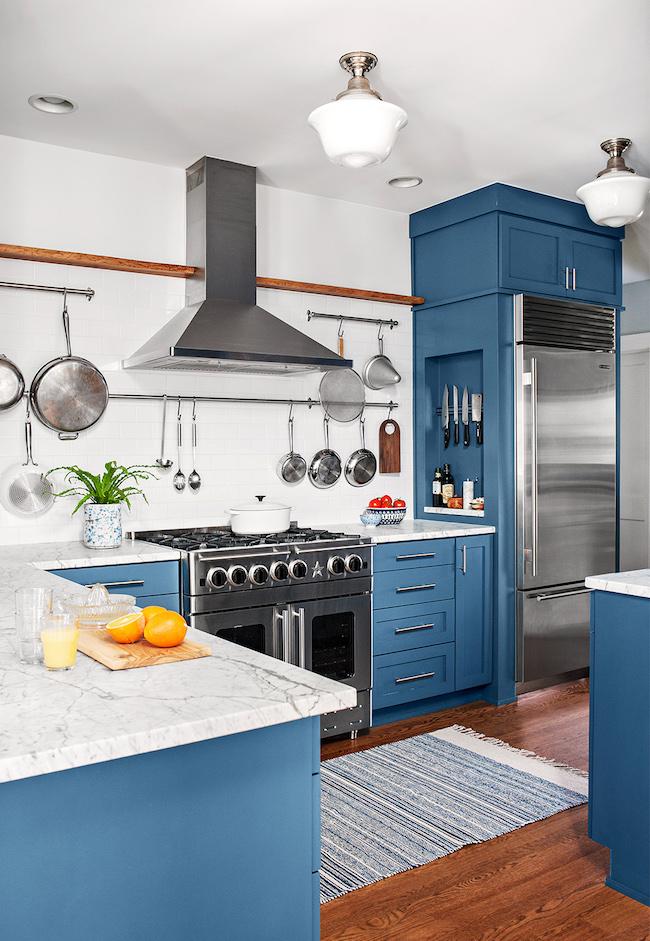 Decoração moderna com armários azuis e bancada de mármore.