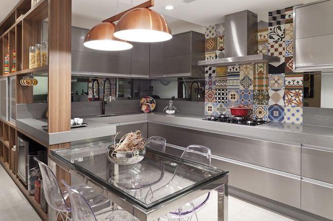 Decoração cinza e moderna com armário de inox, mesa de vidro e ladrilho hidráulico.