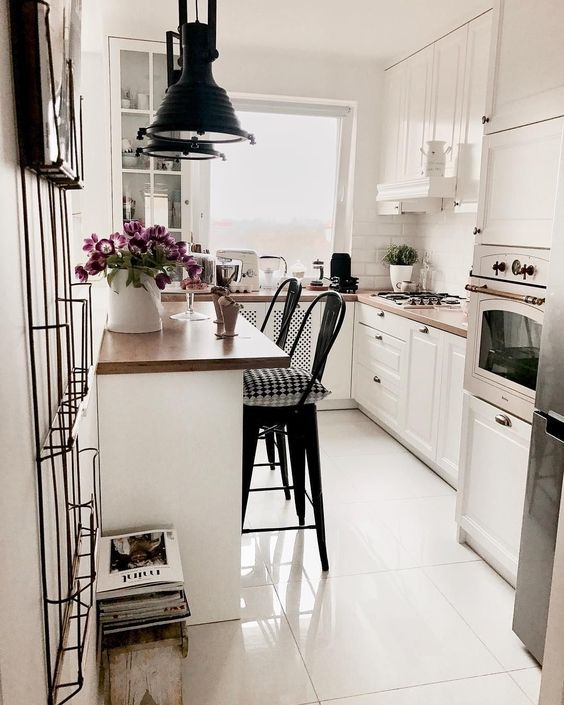 Decoração clean com armário branco, bancada de madeira e luminária moderna.
