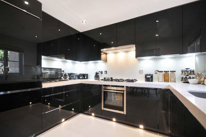 Decoração moderna com armário preto, bancada branca e spots de led.