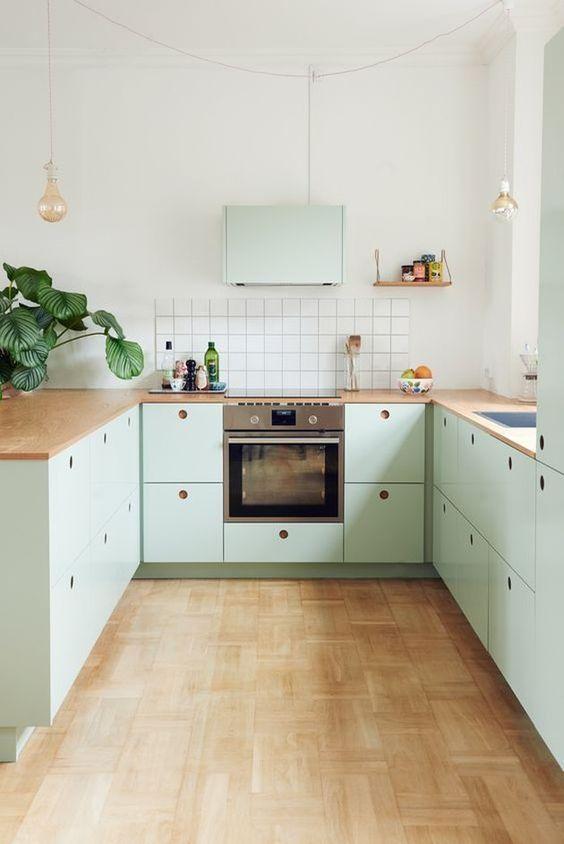Decoração tumblr com armário verde menta e bancada de madeira.
