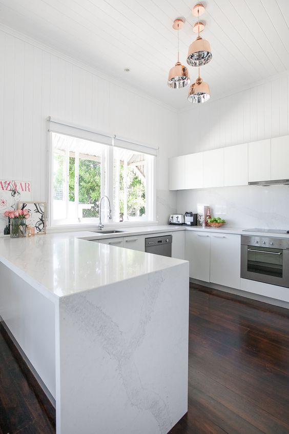 Decoração clean com armário branco, bancada de mármore e lustre moderno.
