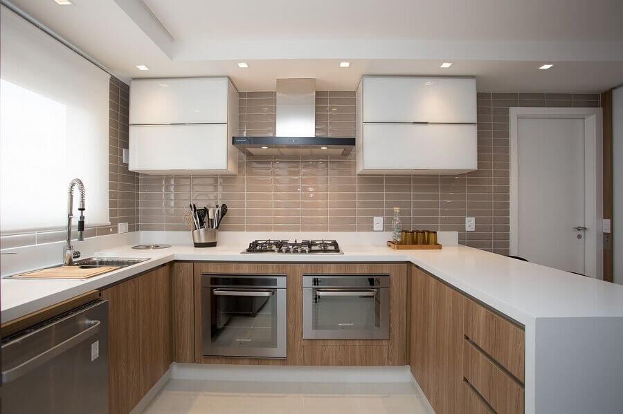 Cozinha planejada em U com armário de madeira e azulejo de tijolinho.