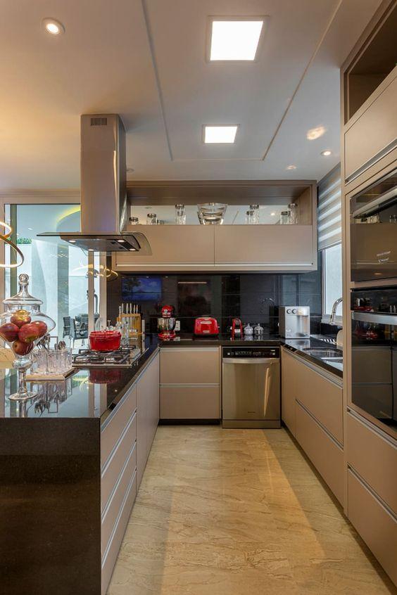 Cozinha planejada em U pequena e com armário bege.