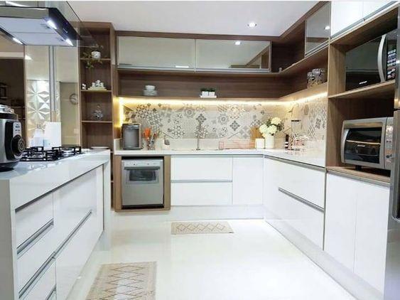 Cozinha planejada em U com ladrilho hidráulico e armário branco.
