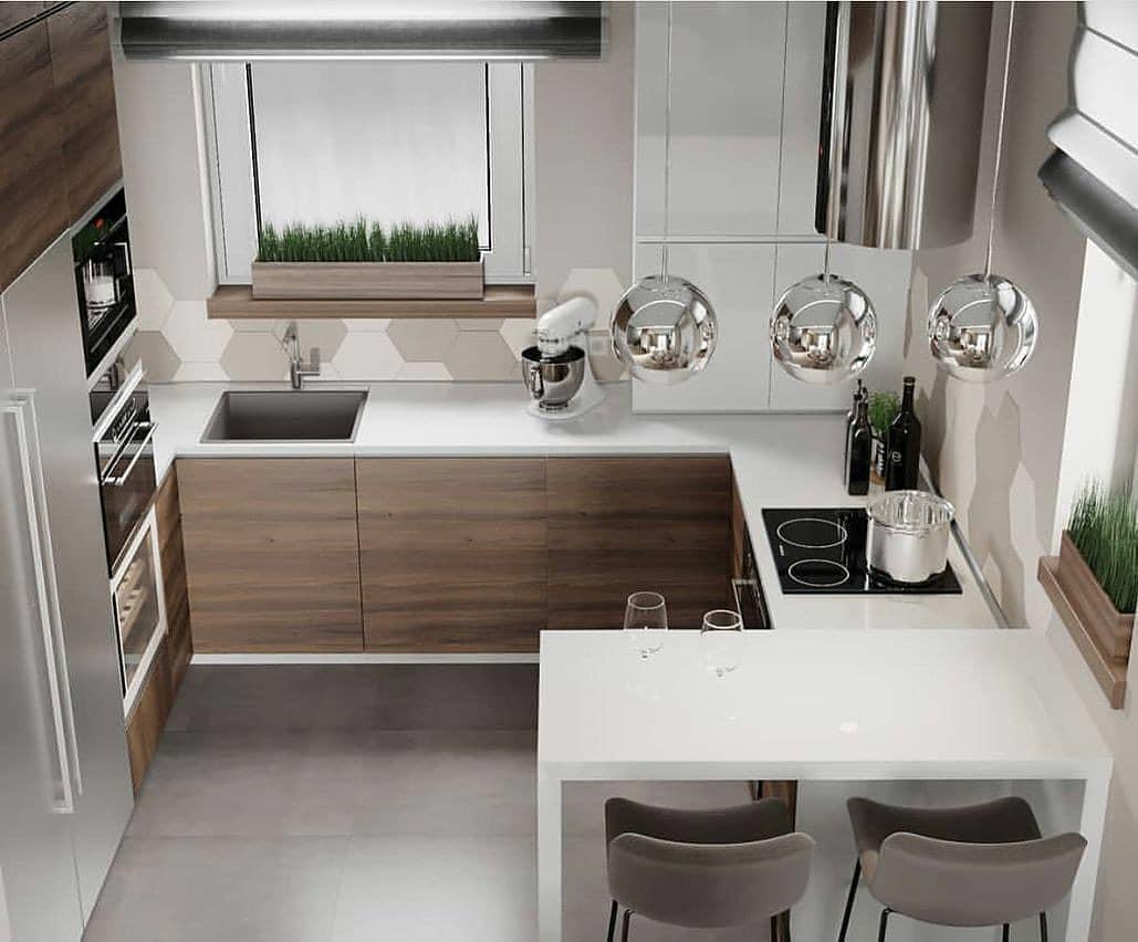 Cozinha planejada em U moderna com pendente suspenso e cooktop.
