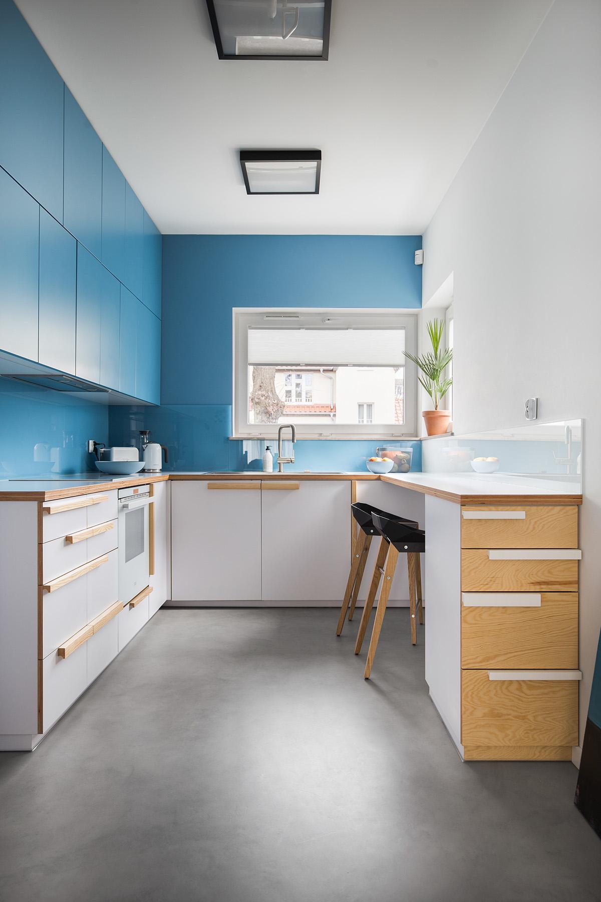 Cozinha planejada em U azul e com armários de madeira.